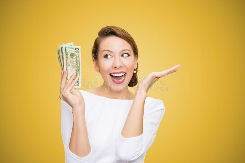 看起来超级愉快在明亮的黄色背景的美元激动的妇女藏品堆  图库摄影