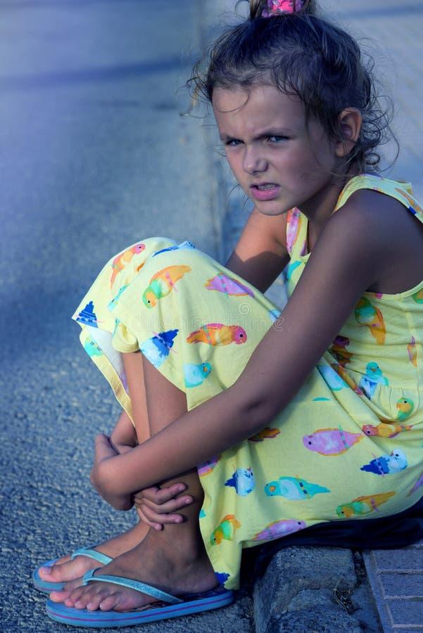 看起来逗人喜爱的女孩哀伤,单独,惊吓,恶习,无家可归者坐地面 晚上时间 好的阳光 1 图库摄影