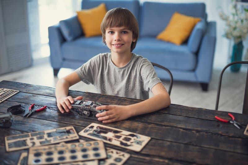 看起来逗人喜爱的男孩愉快,当坐与他的建设者时 免版税图库摄影