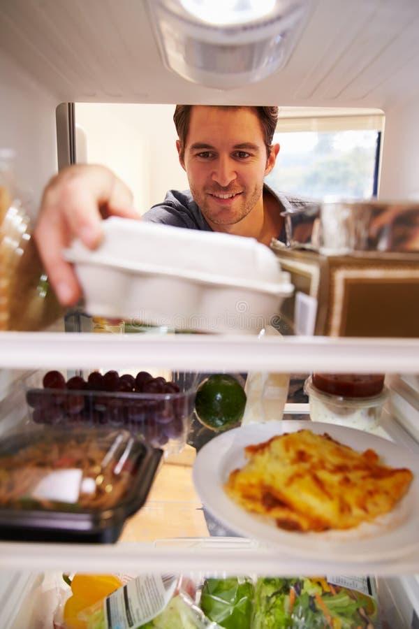 看起来里面冰箱充满食物和选择鸡蛋的人 图库摄影