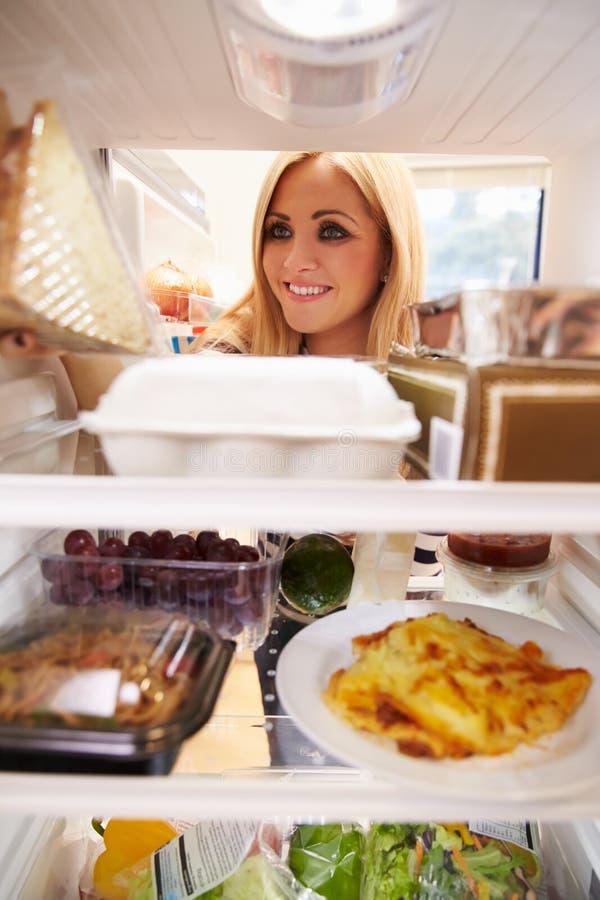 看起来食物里面冰箱和选择三明治的妇女 免版税图库摄影