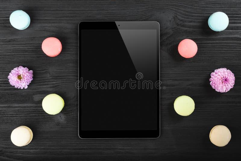 看起来黑片剂的个人计算机类似于ipad和五颜六色的macarons在老黑暗的木背景 库存图片