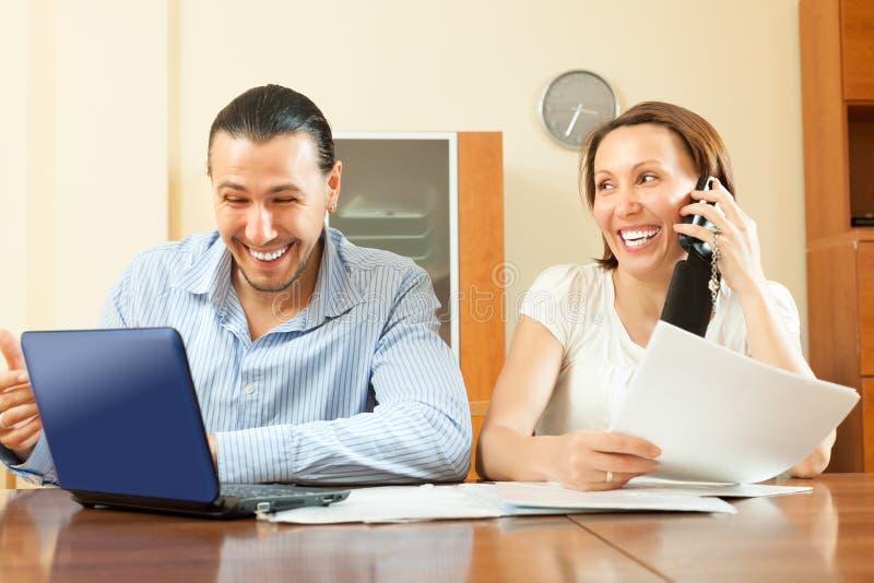 看起来财政文件的快乐的夫妇 免版税库存图片