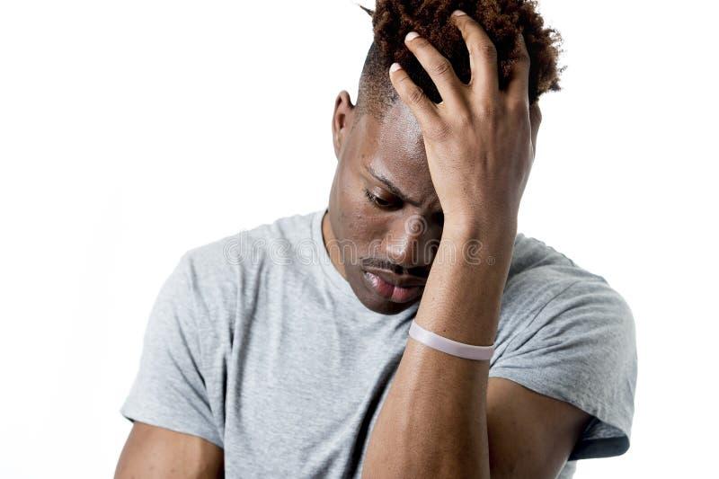 看起来他的20s的年轻可爱的美国黑人的人哀伤和沮丧摆在情感 免版税库存图片