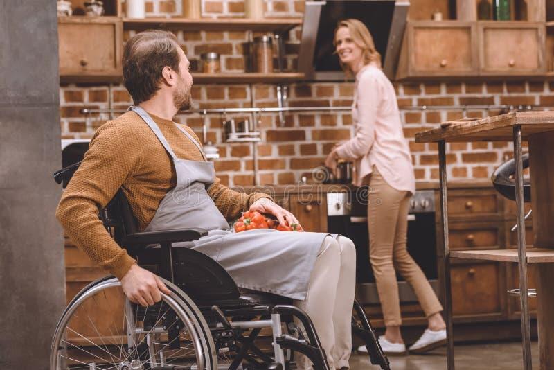 看轮椅的微笑的妇女残疾丈夫拿着菜,当一起时烹调晚餐 库存图片