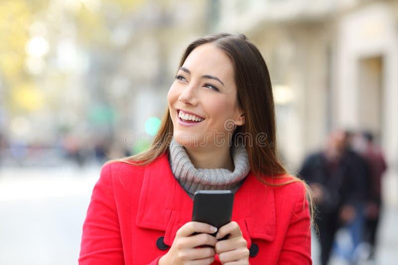 看边的愉快的妇女藏品电话在冬天 免版税库存照片