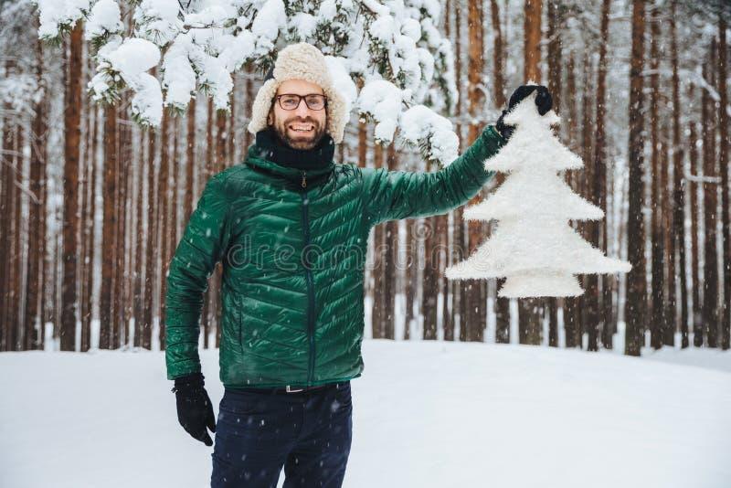 看这棵美丽的杉树!毛皮盖帽的快乐的有胡子的人有耳朵挡水板和绿色滑雪衫的,高兴有步行在冬天前面 库存图片