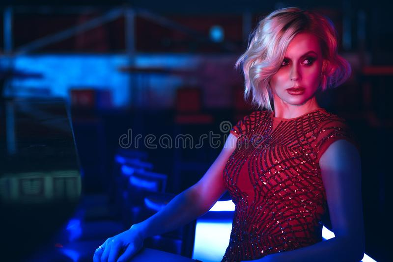 看迷人的白肤金发的妇女坐在夜总会的酒吧在五颜六色的霓虹灯和在旁边 免版税库存图片
