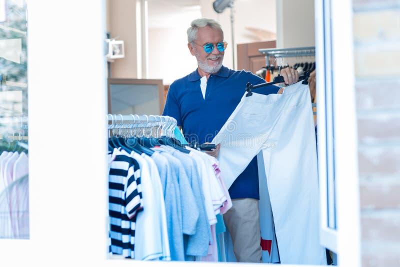 看选上的长裤的高兴年长顾客 免版税库存图片