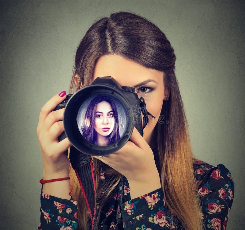 看通过一台照相机的透镜的摄影师与美丽的妇女的它的 库存照片