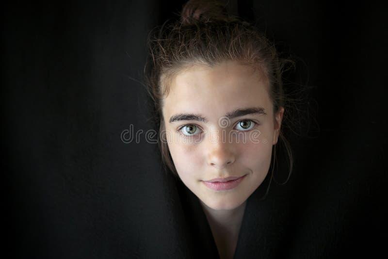 看通过一条黑杂种狗的美丽的十几岁的女孩 免版税图库摄影