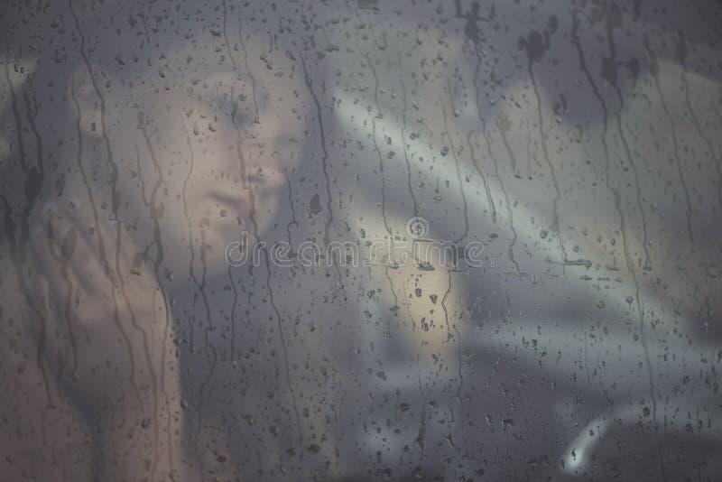 看通过与雨下落的窗口的哀伤的妇女在汽车 年轻女性的面孔在雨车窗后的 库存图片