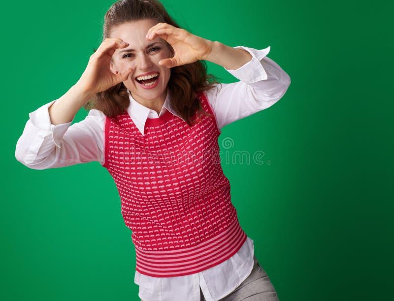 看通过双眼形状的手的微笑的学生妇女 免版税库存照片