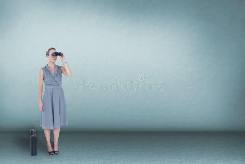 看通过双筒望远镜的妇女反对蓝色背景 免版税库存照片