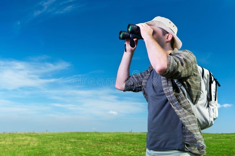 看通过双筒望远镜的探险家 免版税库存照片
