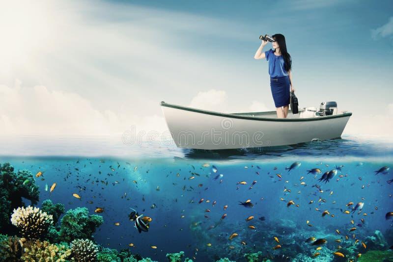 看通过在小船的双筒望远镜的妇女 免版税图库摄影