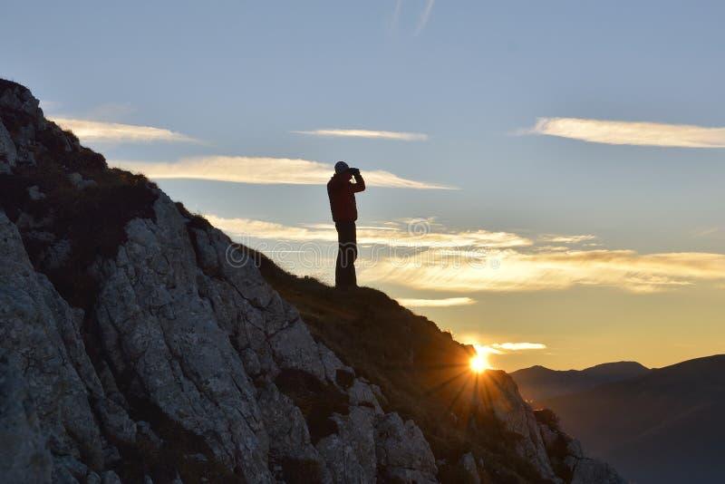 看通过在山的双筒望远镜日落的游人 免版税库存图片