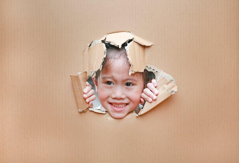 看通过在纸板的孔的愉快的亚裔孩子女孩与拷贝空间 库存照片