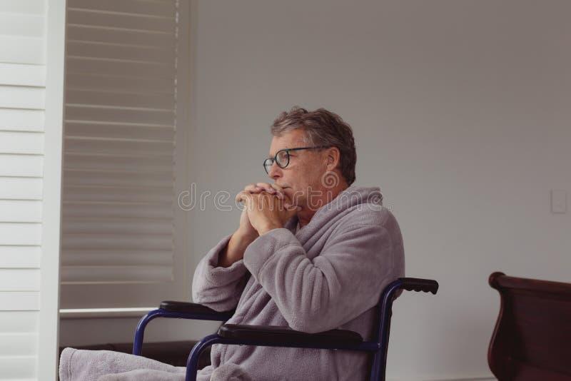 看通过在轮椅的窗口的残疾活跃老人在一个舒适的家 免版税库存照片