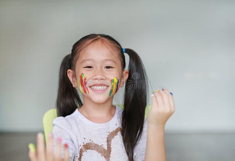 看通过她五颜六色的手和面颊的微笑的女孩画象绘在孩子屋子里 在童颜的焦点 免版税库存图片
