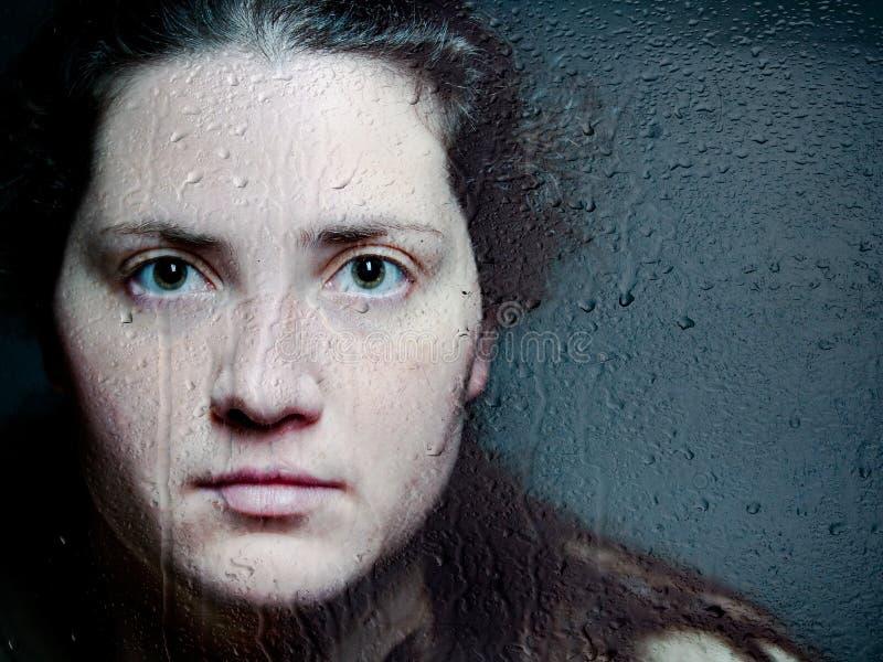 看通过妇女的白种人妇女特写镜头艺术性的画象看通过与水下落和泪花的玻璃 库存照片