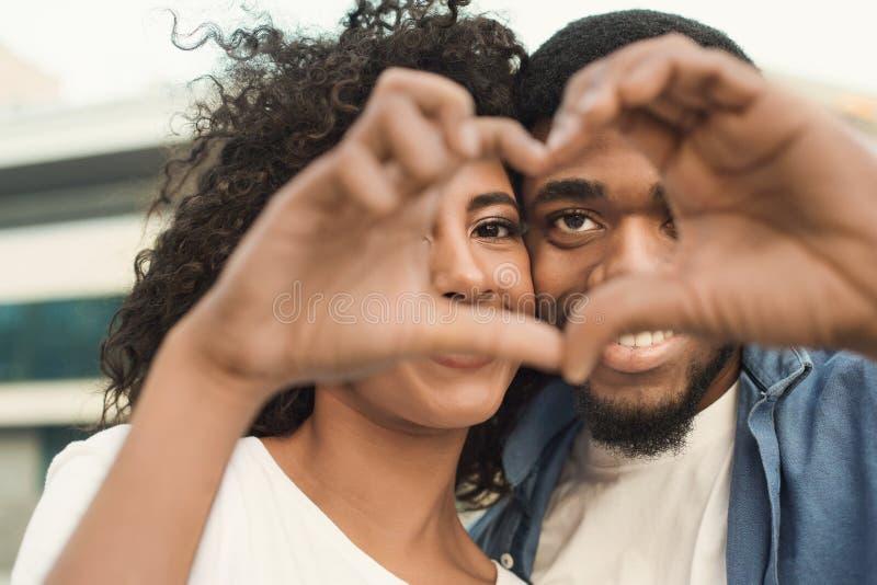 看通过心形的爱的夫妇做用他们的手指 免版税图库摄影