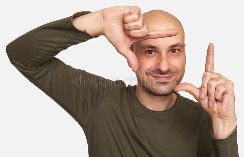 看通过手指框架的秃头人 库存图片