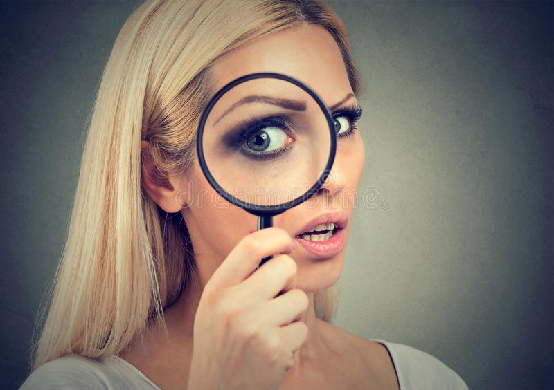 看通过放大镜的好奇少妇 免版税库存照片