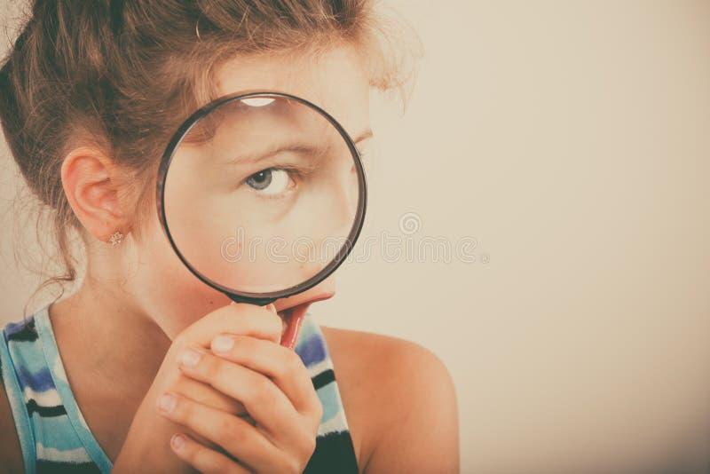 看通过放大镜的小女孩孩子 免版税库存照片