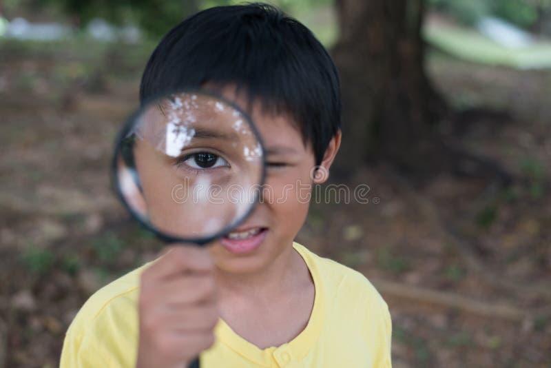 看通过放大镜的年轻亚裔男孩 免版税库存照片
