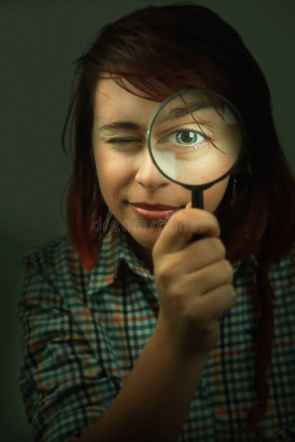 看通过放大镜的滑稽的间谍妇女 免版税库存图片
