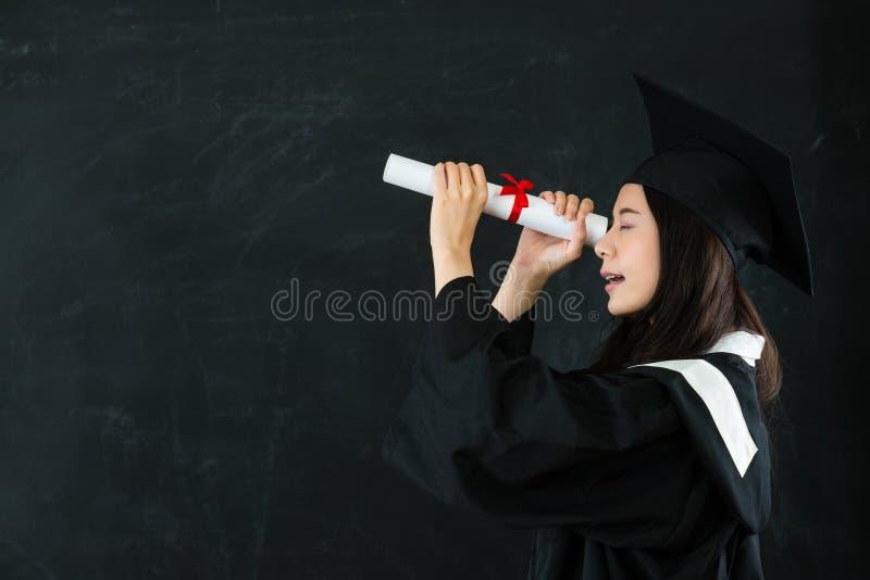 看通过文凭的年轻愉快的毕业 免版税库存照片