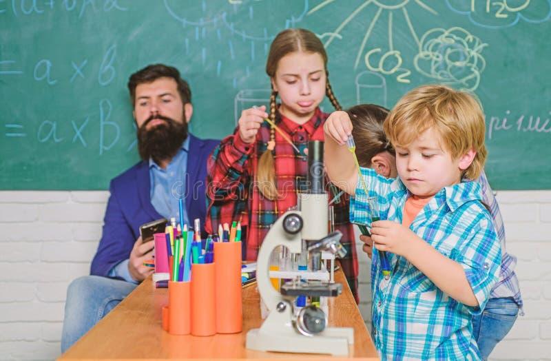 看通过显微镜的学生小学 试验化学制品或显微镜在实验室 免版税库存照片