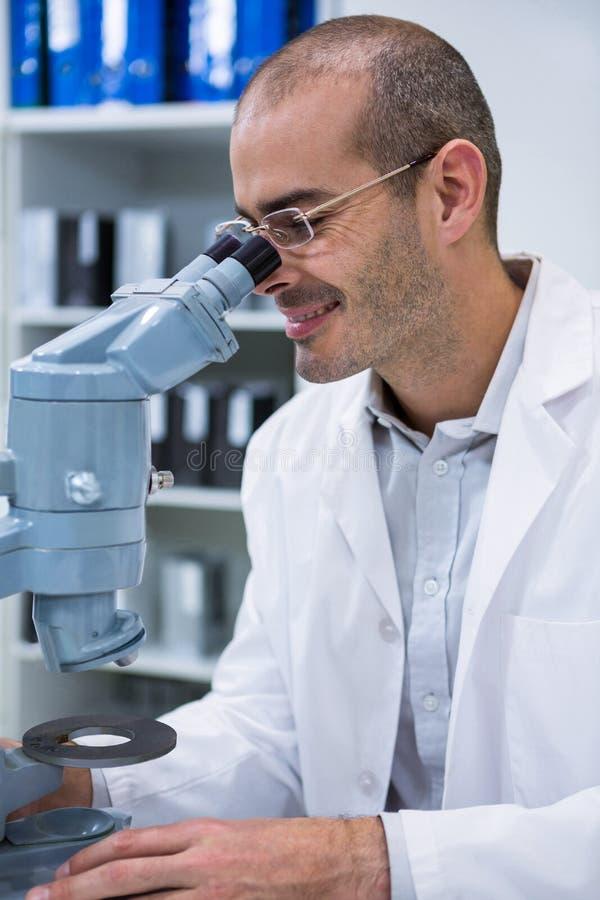 看通过显微镜的微笑的男性验光师 库存图片
