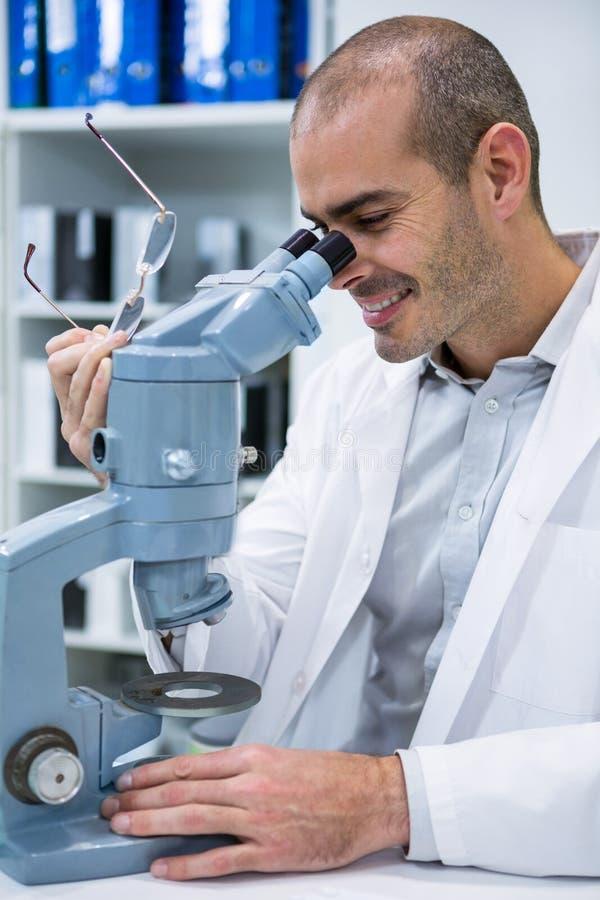 看通过显微镜的微笑的男性验光师 免版税图库摄影