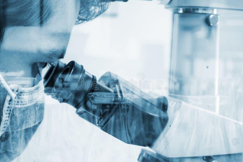 看通过显微镜的科学家为化学测试样品 库存照片