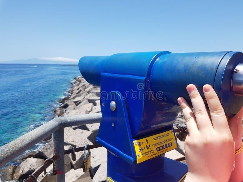看通过横跨海洋的公开蓝色薪水望远镜的人 免版税库存图片