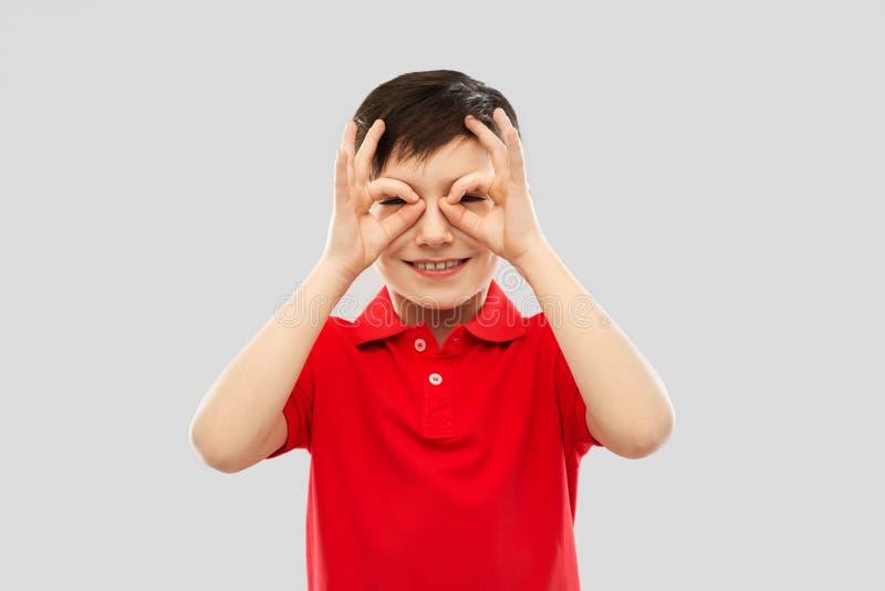 看通过洗指碗的红色T恤杉的男孩 图库摄影