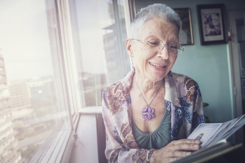 看通过照片的老妇人 免版税库存照片
