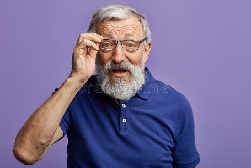 看通过玻璃的快乐的老人照相机 免版税库存照片