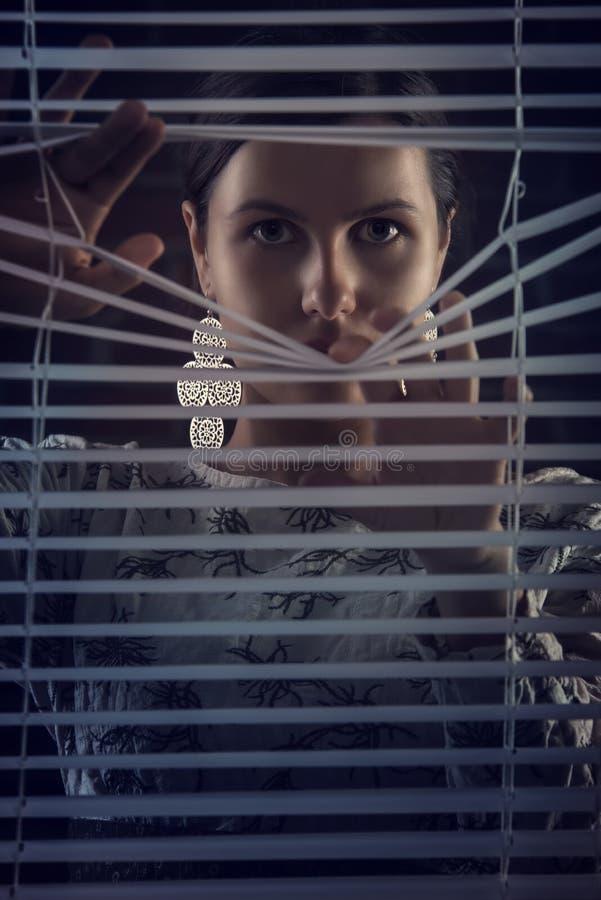 看通过百叶窗,天窗的美丽的神奇妇女画象  免版税图库摄影