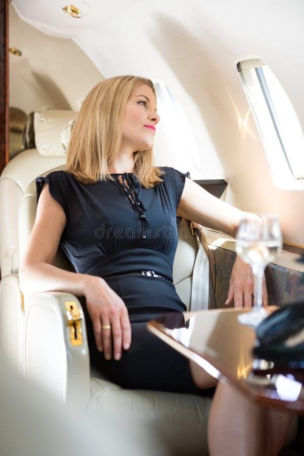 看通过私人喷气式飞机的窗口的妇女 免版税库存照片