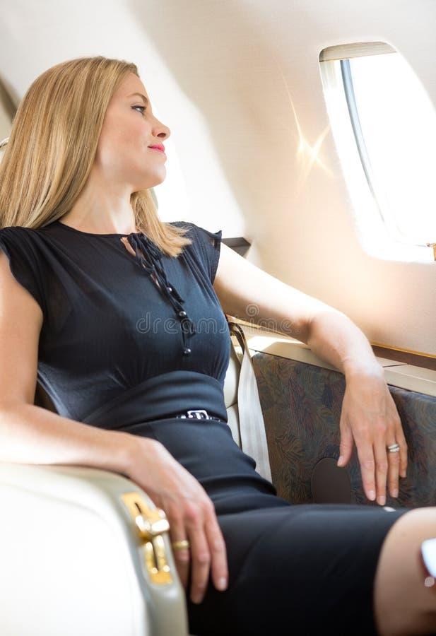 看通过私人喷气式飞机的窗口的富有的妇女 免版税库存图片