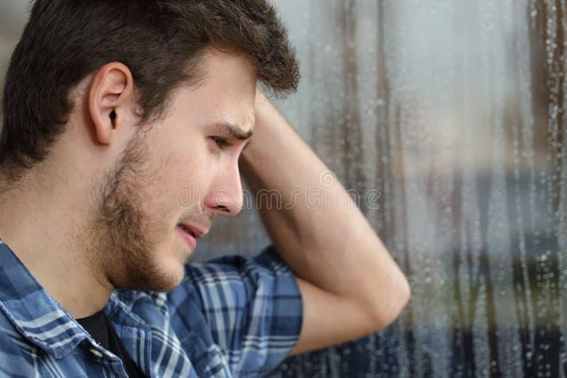 看通过窗口的哀伤的人每雨天 图库摄影