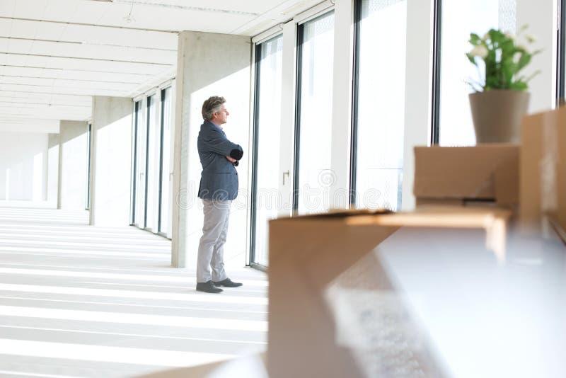 看通过窗口的成熟商人侧视图在新的办公室 免版税库存照片