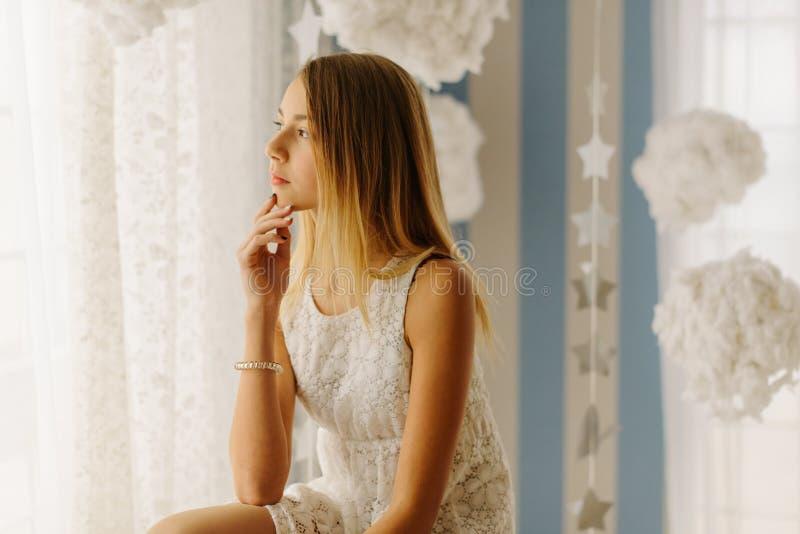 看通过窗口的年轻十几岁的女孩的旁边画象 免版税库存图片
