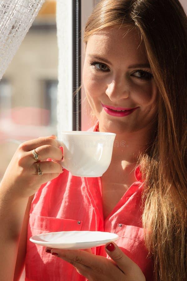 看通过窗口,放松的饮用的咖啡的妇女 免版税库存图片