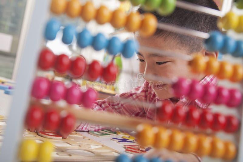 看通过算盘解决难题的男孩 免版税图库摄影