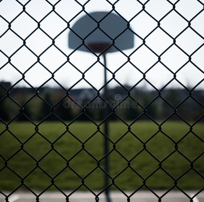 看通过篱芭由后照的篮球场 免版税库存图片