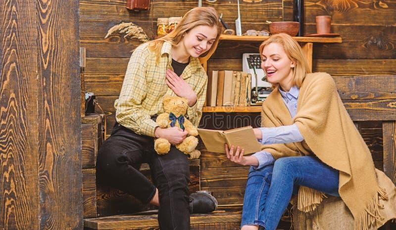 看通过老家庭册页的妈妈和十几岁的女孩 妇女和她的女儿微笑的一会儿看书,幸福和 库存照片